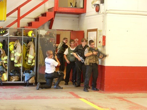 Explorers and instructor looking around a corner in a fire house