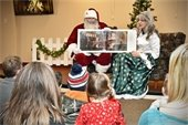Santa and Mrs. Claus reading Polar Express at the Baker Free Library