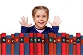 A little girl standing behind encyclopedia books that reads never stop learning