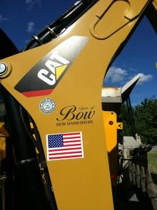 A piece of Public Works equipment bearing an American Flag and the Bow logo.